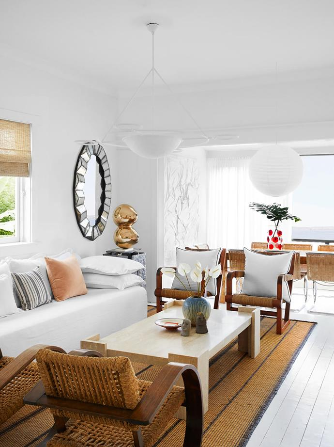 The living room's calm, pared-back palette contrasts with the colourful beach views beyond. 1940s rope armchairs by Adrien Audoux and Frida Minet and custom coffee table by Tamsin Johnson on a vintage Tuareg mat. Brass sculpture by Sanné Mestrom. 1930s French mirror. Pendant light by Anna Charlesworth.