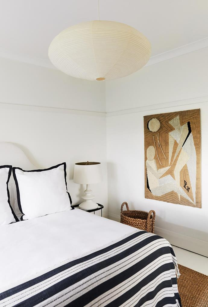 The second bedroom has a custom plaster lamp and a bedhead by Tamsin Johnson with a vintage Indian bedspread and a 1940s French abstract tapestry.