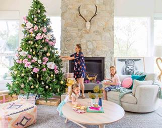 Woman decorating Christmas tree in living room with two daughters