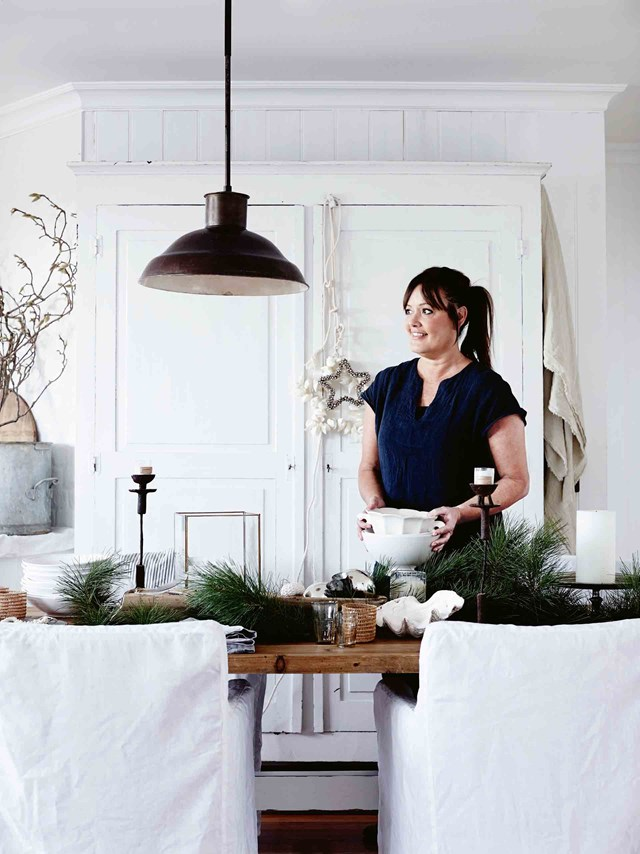 Michelle sets the Christmas table with pine foliage and seaside decorations in her rustic coastal home.