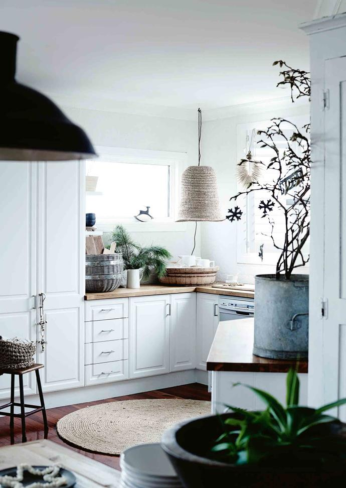 """The revamped kitchen has new cupboard handles, timber benchtops and a woven sisal hanging lamp made in South Africa and bought at [Greedilulu](https://www.greedilulu.com/
