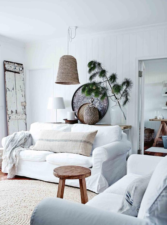 Neutrals on white, basketry, loose linen covers and other natural fibres create a relaxed look in the downstairs sitting room of the Woodses' family home in Mornington, Victoria. The large metal tray belonged to a friend — a chair was swapped for it.