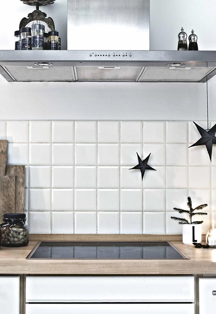Branches and decorations are hung from the ceiling to create a winter wonderland in the mostly white room.<br><br>**Kitchen** A silver Nordal tray and decorative stars adds sparkle on the side of the sink.