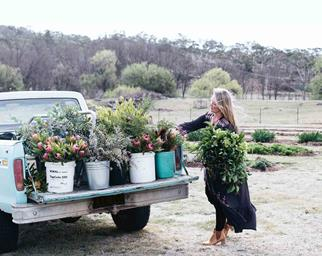 Woman loading flowers onto back of ute