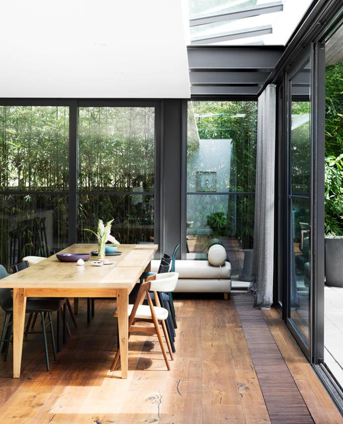 Foor-to-ceiling glass on two sides of the space delivers the indoor-outdoor connection the owner desired. The mix of vintage and contemporary dining chairs is an example of the owner's preference for eclectic decor. The dining table is almost 4m long – ideal for accommodating extended family. The trench grill for the hydronic heating was custom made.