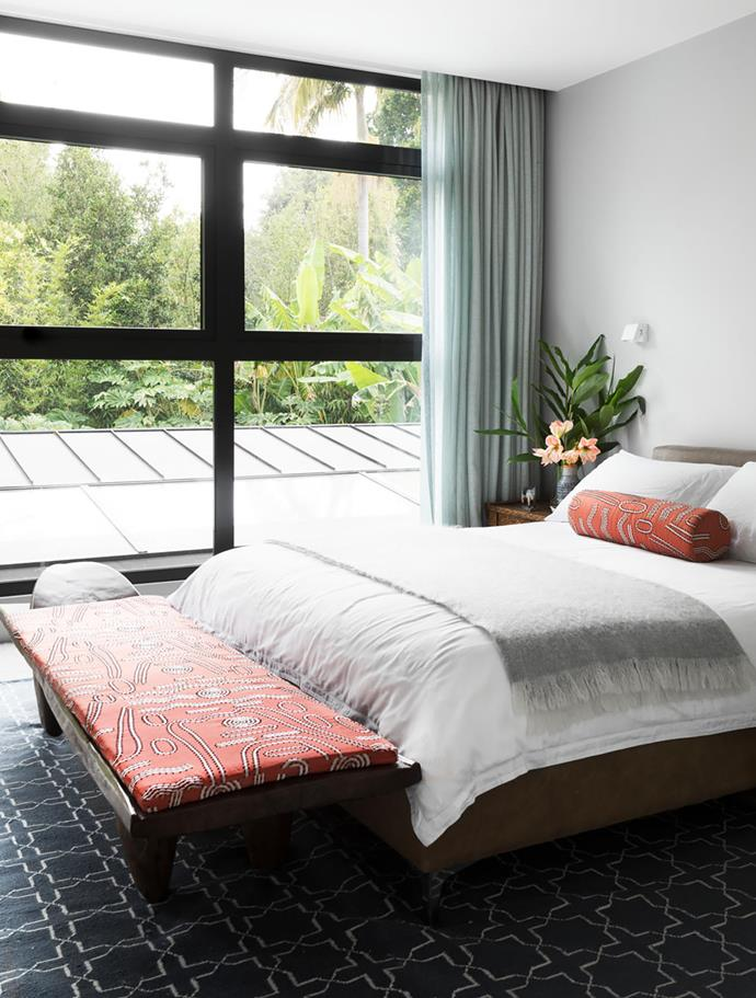 Thanks to a new wall of windows, views of the garden can be enjoyed from bed. Bolster and bench covered in owner's own fabric. Curtains by Interior Solutions. For similar rug, try Temple & Webster.