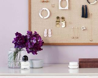 Dressing table with perfume, purple flowers. A jewellery pin-board hangs above.