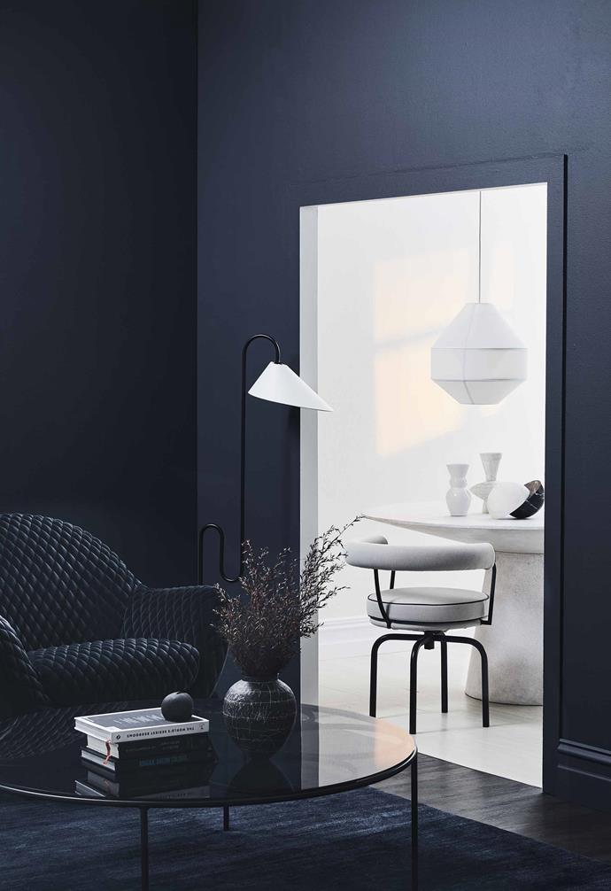 "Choosing [the right shade of dark paint](https://www.homestolove.com.au/best-dark-paint-colours-20169|target=""_blank"") will make a world of difference to creating a warm and moody cocoon in your home. In this living room space the blue undertones of the dark feature walls add an extra dimension to the room."