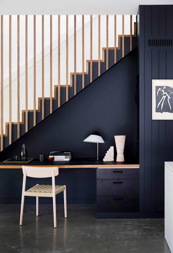 "The study space in this [nature-inspired home in Riverview](https://www.homestolove.com.au/nature-inspired-house-riverview-20198|target=""_blank"") was painted in Dulux Black, designed to help the nook completely disappear into the staircase above."