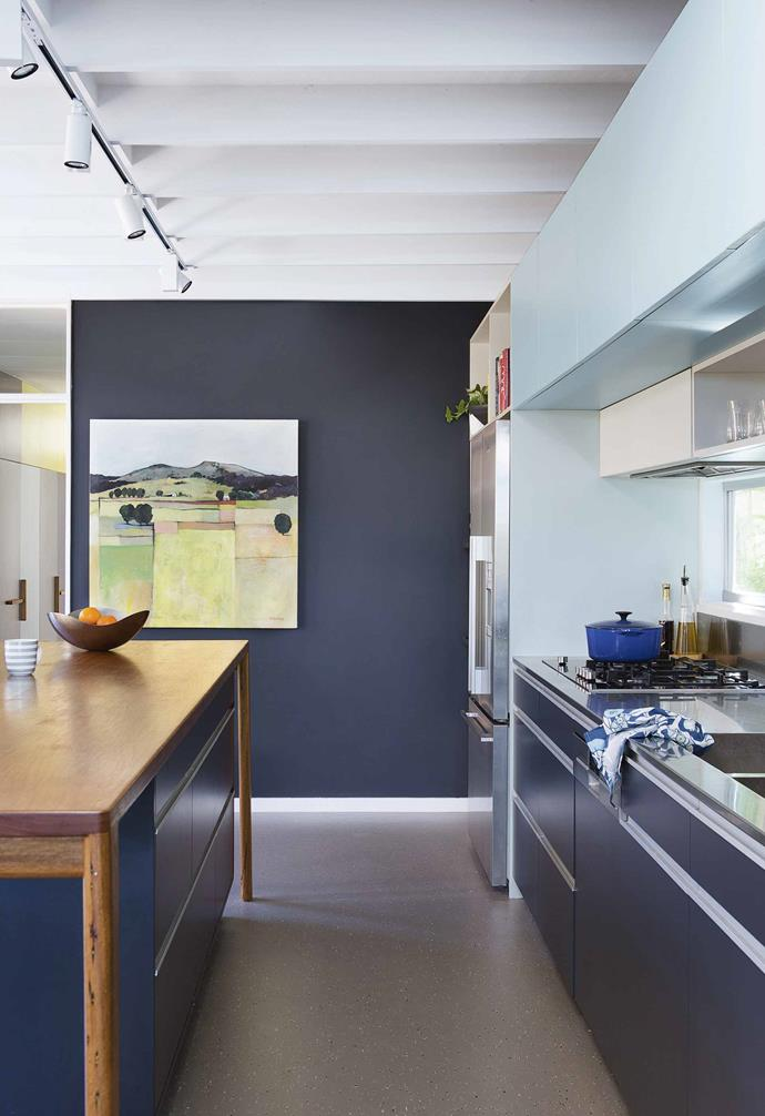 "A midnight blue feature wall in the kitchen of this [Modernist-style Sydney home](https://www.homestolove.com.au/modernist-sydney-home-renovation-17570|target=""_blank"") perfectly complements the dark kitchen cabinetry, transforming the space into a cosy alcove within an open-plan living environment."