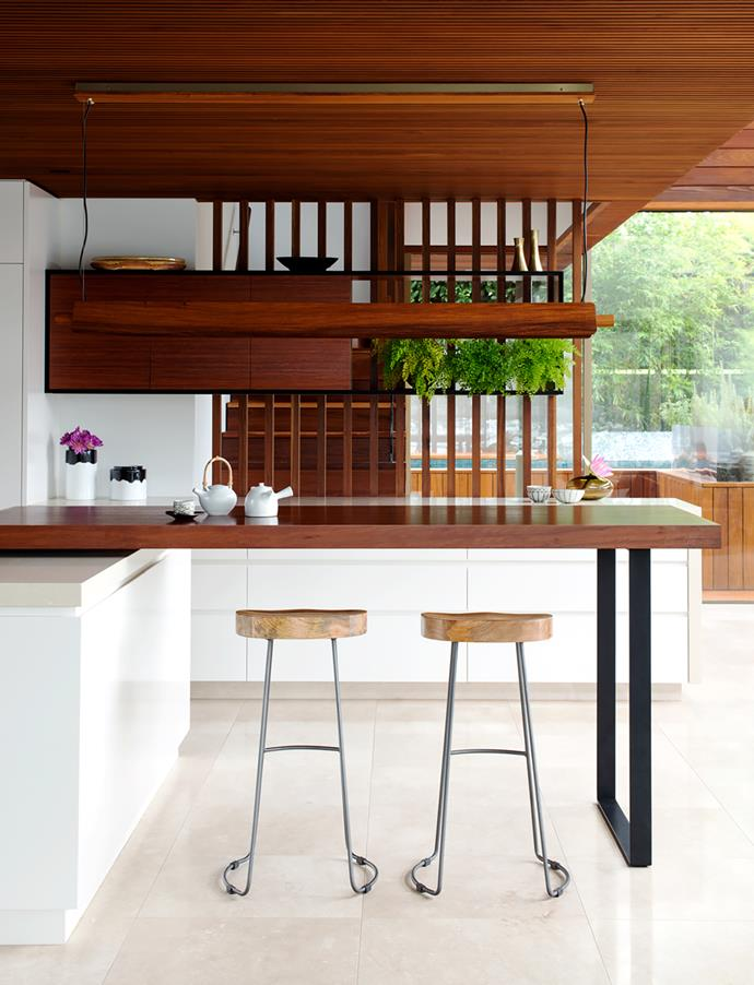 Timber is used throughout the house to create warmth and a Bali-like feel. Batten screens separate the spaces without compromising the feeling of openness. Teapot from Planet. Torremato 'Ram' suspension light from LightCo. Benches in Caesarstone in Buttermilk and 'Lamiwood' in Chamois from Laminex.