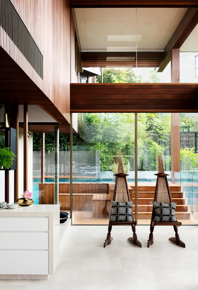 The main living room has a double-height void fronting onto the water on one side and the pool on the other. Chairs bought in Bali. Creme Royale stone on floors from Calibre Tiles.