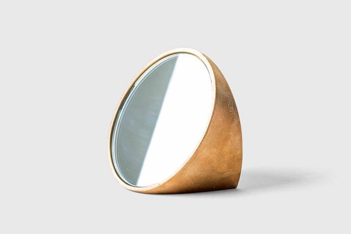 "S/N Brass mirror, $150 USD, [Marie Kondo](https://shop.konmari.com/collections/decor-living/products/konmari-decor-bath-s-n-brass-mirror target=""_blank"" rel=""nofollow"")."