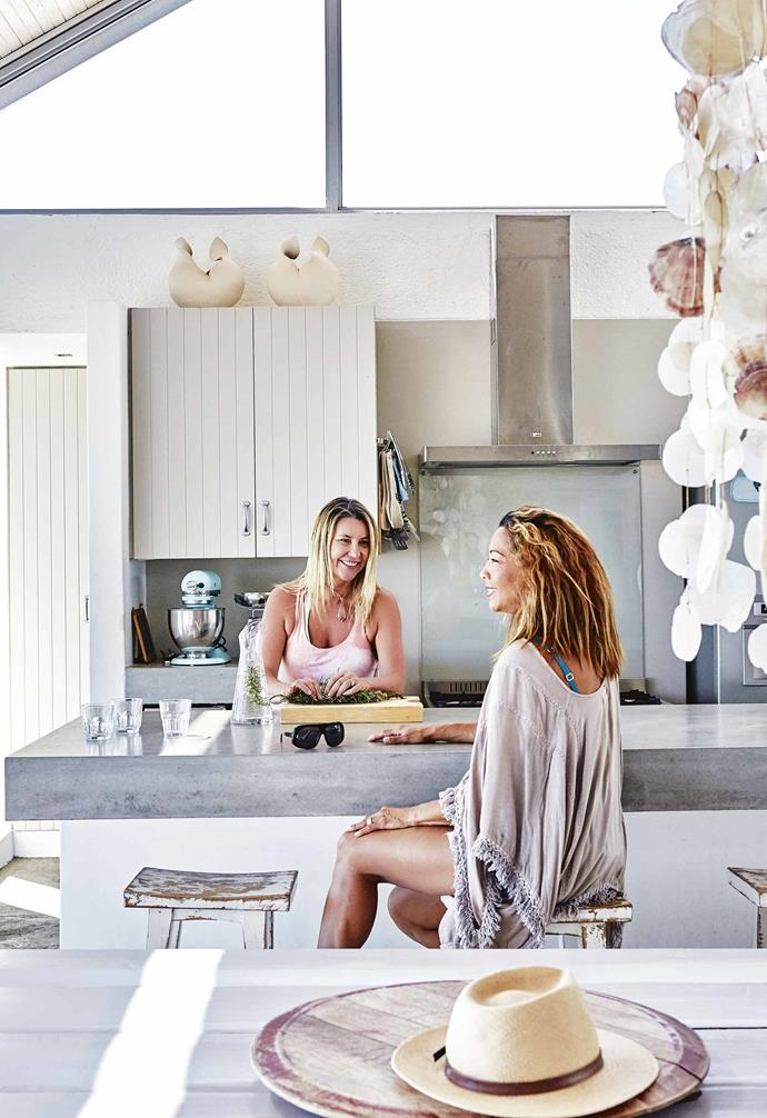 """What was initially a purely practical decision has in fact had a profound impact on the way you experience the space – the kitchen and living area are edged by water on both sides as a result. The glass doors on either side open up completely, which Caroline says makes it feel you are """"living on a boat"""".<br><br>**Kitchen** Owner Caroline prepares lunch with her friend Veronique."""