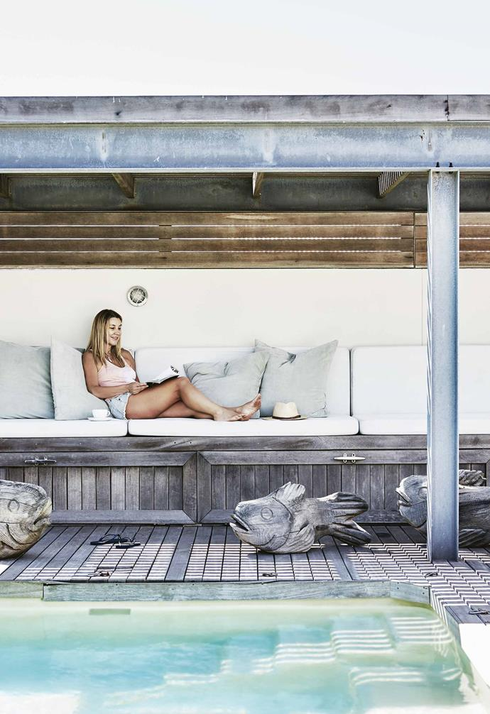 The house sits on an isolated 630 square-metre plot, but the entire property is decked (another solution to thwart the wind and sand). A recent addition to the home is a square 'book nook' that perches on the beach-fronted deck, providing a sunny sanctuary and a place where guests can retreat.<br><br>**Pergola** Owner Caroline stretches out under the sheltered awning by the pool. She purchased the driftwood fish from a travelling salesman.