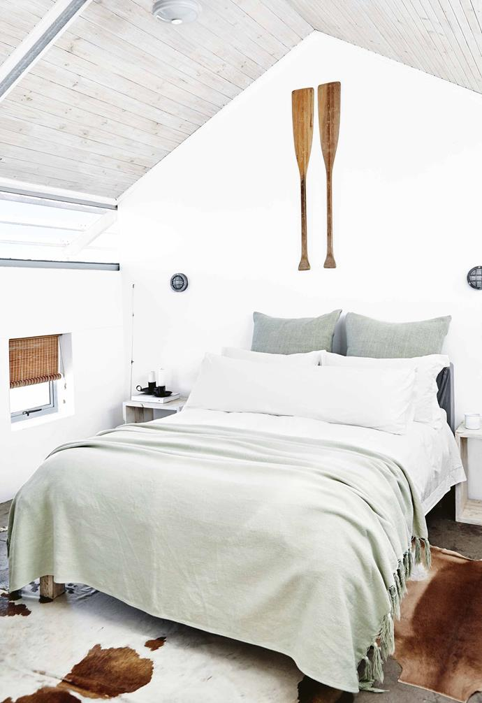 The home is designed for friends to holiday together without feeling cramped: the bedrooms are divided into separate zones. On the lower floor, there are two bedrooms and a bathroom.<br><br>**Bedroom** Soft white and timber decor gives the bedroom a relaxed feel, enhanced by the muted green linen from Weylandts. Marine bulkhead wall lights add to the seaside vibe.