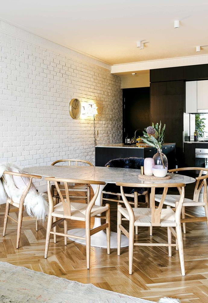 "**Where did you start on the decorating front?** <br><br>I started with the existing elements – the [exposed brick walls](https://www.homestolove.com.au/7-kitchen-designs-with-exposed-brick-18350|target=""_blank"") and oak parquetry floor. Since they are really the heroes, I needed to find neutral furniture pieces, but with interesting shapes so the whole thing wasn't boring. I also wanted to make the most of the sun from the balcony; that was another reason to keep the colour palette light.<br><br>**Open-plan living** The living area, dining area and kitchen are divided with furniture placement and layout choices. The material mix of painted brick, oak parquetry flooring and laminate cabinetry is given further depth with a variety of accessories. Tactile cushions and polished details complete the look."
