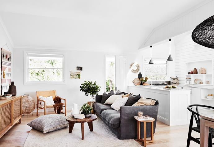 The open-plan living, dining and kitchen area has a crisp white backdrop and neutral and black furnishings. The sofa is from Uniqwa.