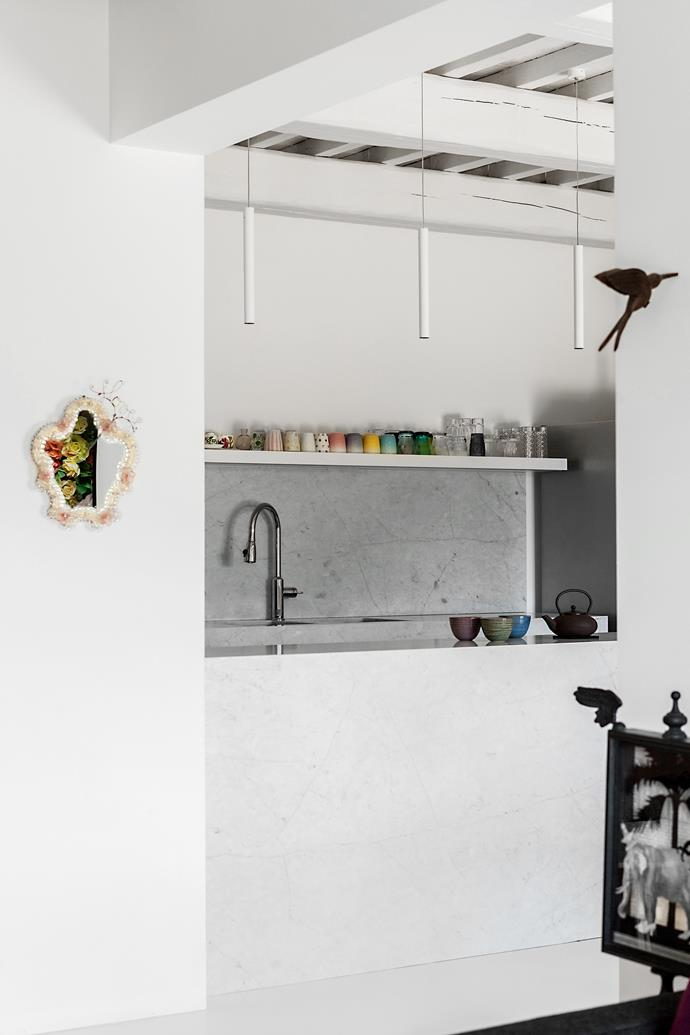 Designed with white walls, Carrara marble surfaces and no doors, the kitchen flows into the open living space.