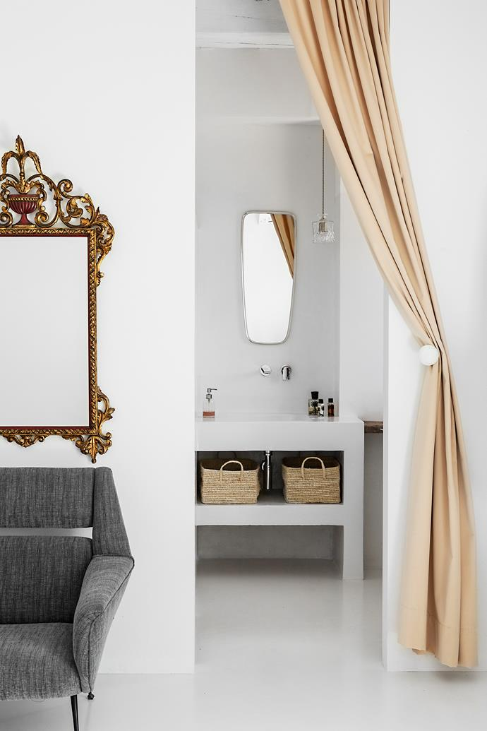 A pink velvet curtain separates Doris's bathroom from her bedroom. Here, the decor is more refined and feminine than the rest of the house. The chic pendant lamp is by product designer Lee Broom. The elaborate mirror and grey armchair are vintage.