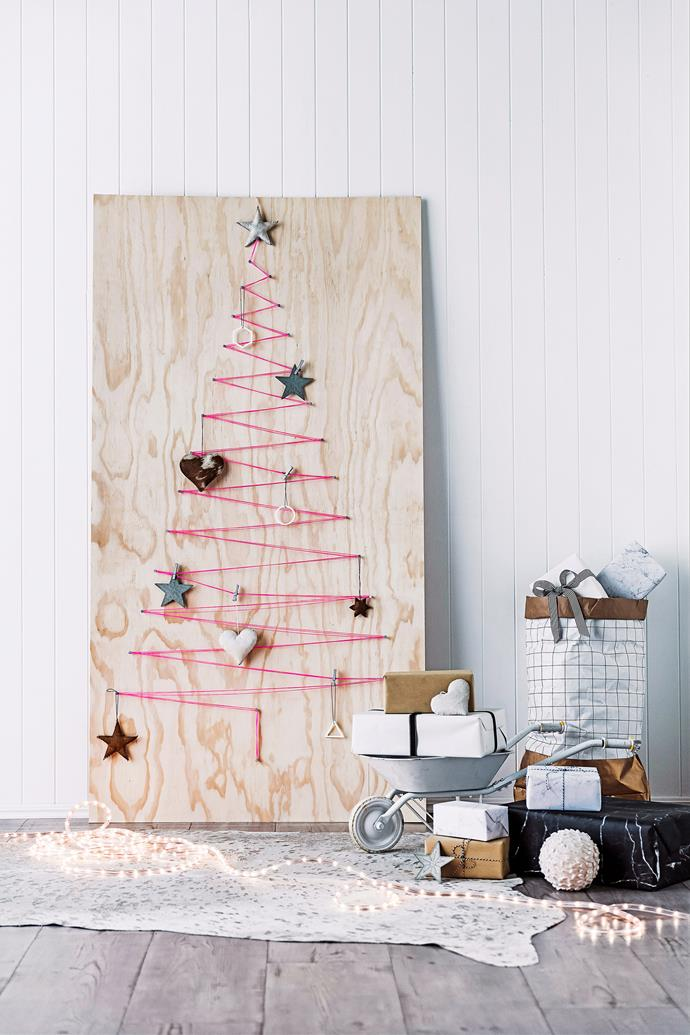 "**Zig-zag Christmas tree:** Another plywood design (minus the sawing). Simply purchase a pre-cut piece of plywood from your local hardware store, attach nails or thumb tacks in a triangle/tree outline and then zig-zag some coloured thread or wool from nail to nail to create a [Christmas tree](https://www.homestolove.com.au/christmas-tree-decorating-tips-2611|target=""_blank"") like the one pictured. Hang decorations off the nails and secure a star at the top!"
