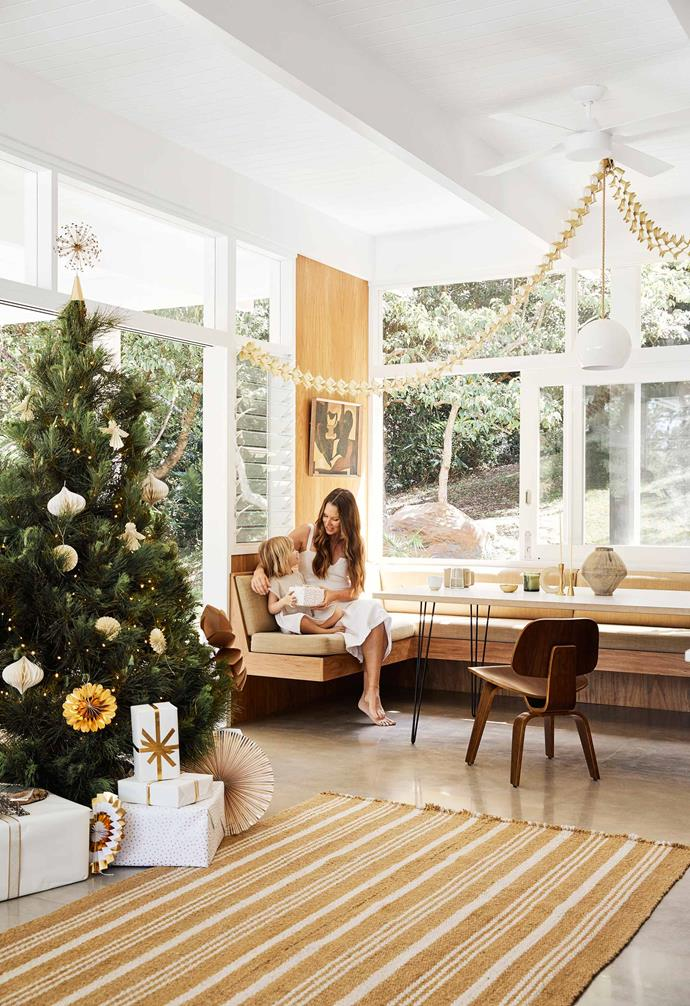 "**Dining area** Megan and daughter Maple in a cosy corner among the Christmas decorations. Those on the tree are mostly made by the family, with extra flourishes and wrap from [Officeworks](https://www.officeworks.com.au/|target=""_blank""