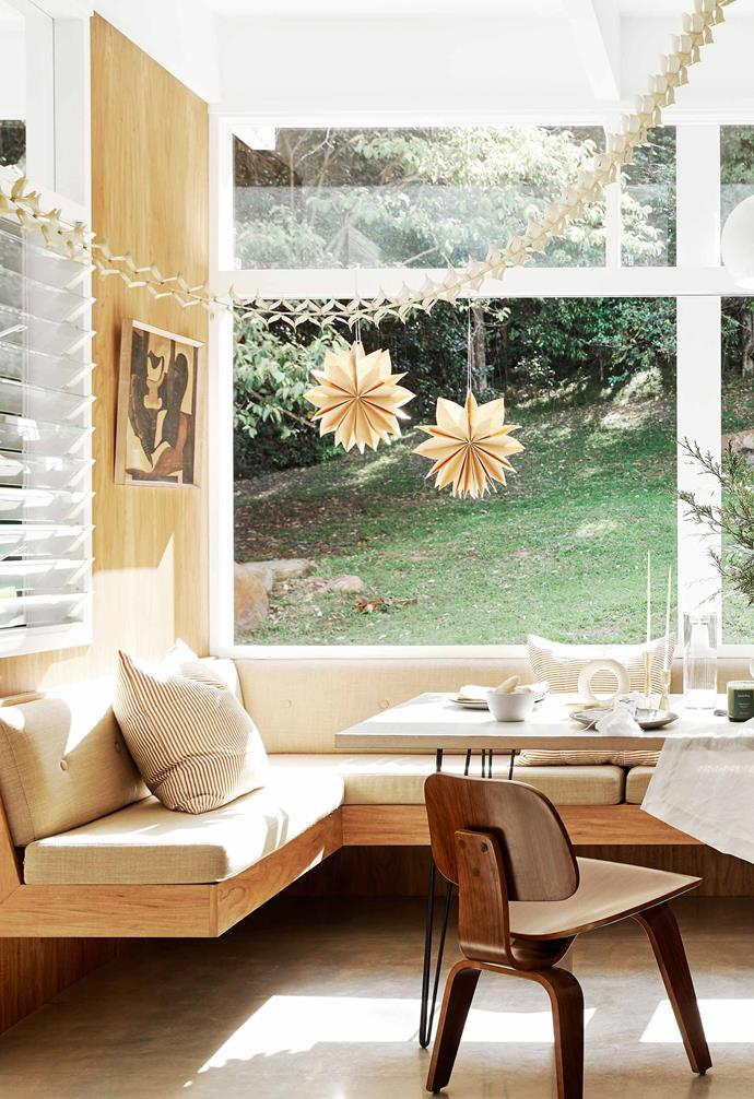 "**Built-in seat** This gathering point looks out to the grassy slope at the back. The diner-style seating was designed by Mike, who also made the dining table. ""I love built-in furniture and the old-school look and feel of a banquette,"" says Megan. Striped cushions and Lumira candle, [The Flower Bar](https://www.theflowerbarbangalow.com.au/