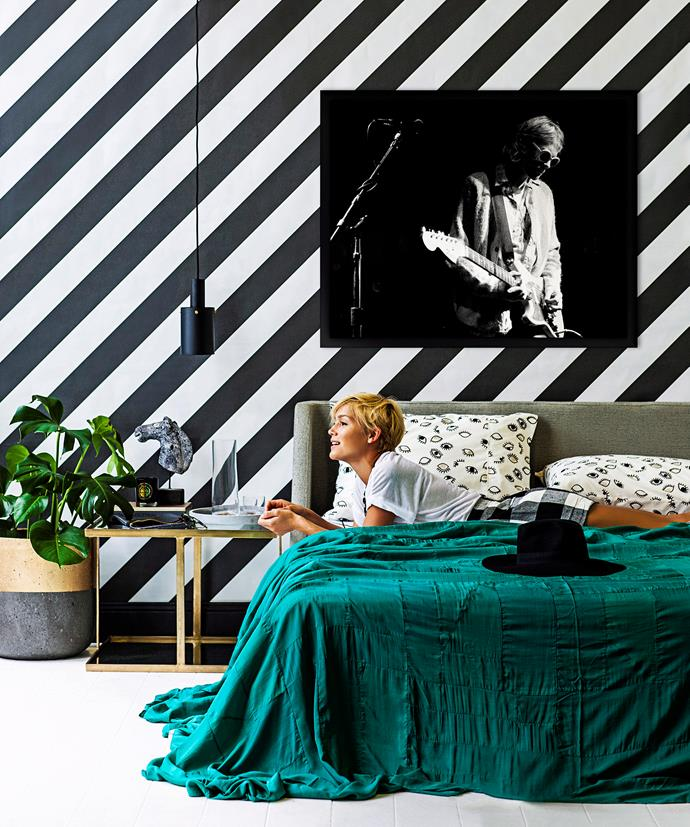 An emerald green bedspread pops against this monochrome striped feature wall.