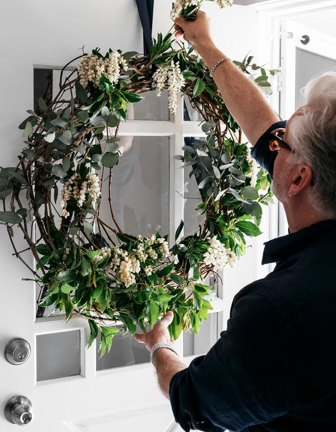 The front door is dressed with a willow wreath embellished with fresh foliage from the garden.