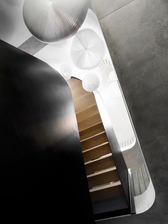 A sinuous gleaming steel staircase snakes its way up through the three storeys of the house.