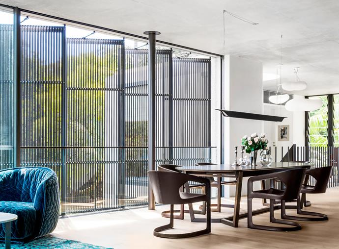 To maximise light and privacy, louvred panels of fine timber battens specially blackened using a traditional Japanese method were installed. Surrounded by Minotti 'Twombly' chairs from De De Ce, the 'Atticus' dining table by Lowe from Hub can be extended if needed. Foscarini 'Troag' pendant light from Space. Moroccan Beni Ourain floor rug in Aqua from Cadrys. Moroso 'Redondo' armchair and Molteni&C 'Domino' coffee table, both from Hub.