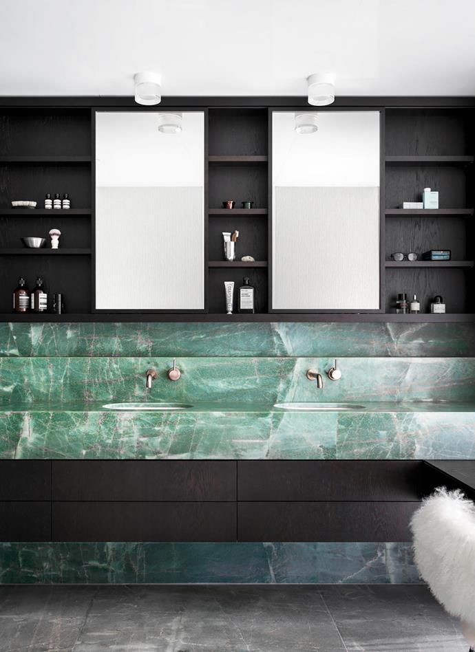 The bathroom is washed in soft mint-green marble and dark chocolate joinery.