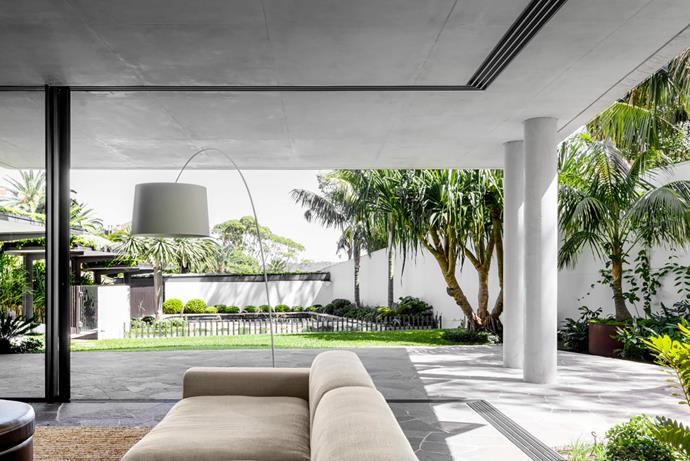 Baxter 'Nepal' chair from Criteria. Doors roll away to open up the ground floor, creating a covered outdoor space with a custom-made modular sofa and leather ottoman on an Abaca 'Manzanilla' woven rug from International Floorcoverings. Foscarini 'Twiggy' floor lamp from Space.