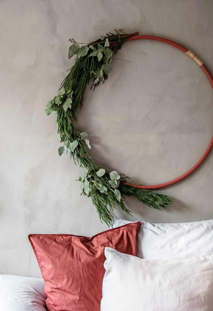 **Main bedroom** To prepare for Christmas, Rikke Graff Juel spray-  painted one of her daughter's hula hoops and added thuja and eucalyptus branches and ribbons.