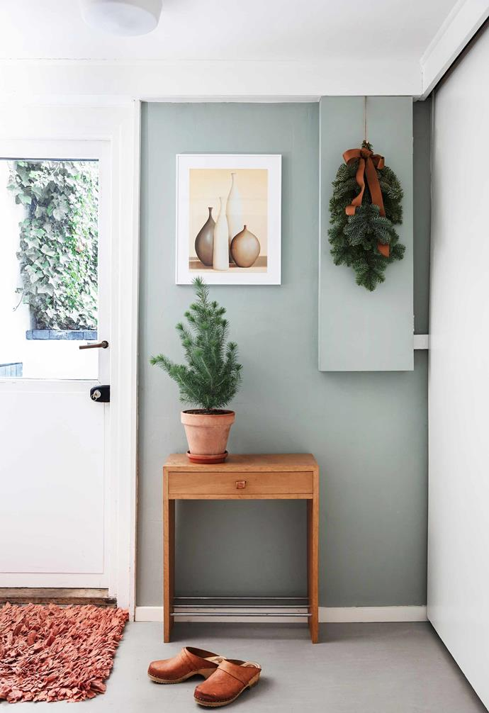 **Rear entry** More soft tones with a 1950s side table, walls painted in Dyrup English Mist and a print by Arlene Stevens. Spread cheer throughout your home by turning existing potted plants into mini Christmas trees. Rikke has done this with thuja plants placed on her hall table, in the kitchen, and on the tops of cabinets