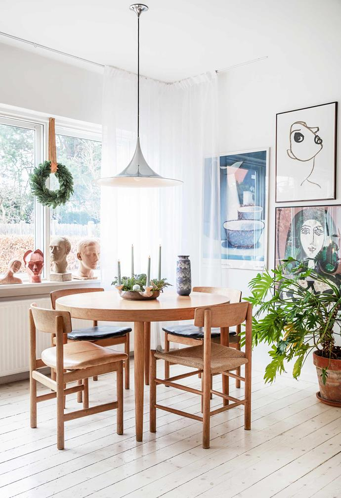 **Upstairs dining space** A Gubi 'Semi' pendant light hangs above a classic Børge Mogensen dining setting. Rikke collected the busts at flea markets. More of her exhibition posters are displayed on the wall.
