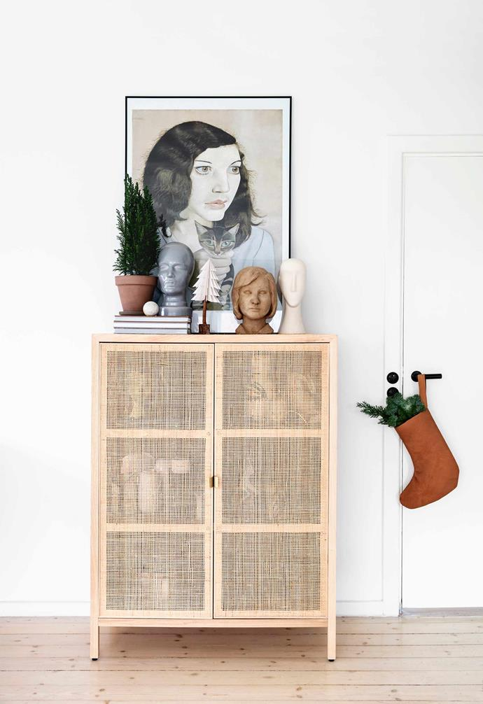 """**Living area** The rattan cabinet is an Ikea piece called the Stockholm 2017. Rikke found the poster at ARoS Art Museum in Aarhus, Denmark. Rikke even made her own leather [Christmas stockings](https://www.homestolove.com.au/how-to-make-your-own-christmas-stocking-4396