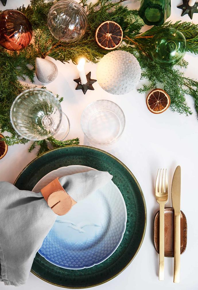"""**Downstairs dining area** Leather and spruce details set the mood, with green plates from Bitz, Ilva cutlery and glasses from flea markets. Rikke has used leather for several decorations, including her own [napkin rings](https://www.homestolove.com.au/how-to-make-a-christmas-napkin-ring-10401