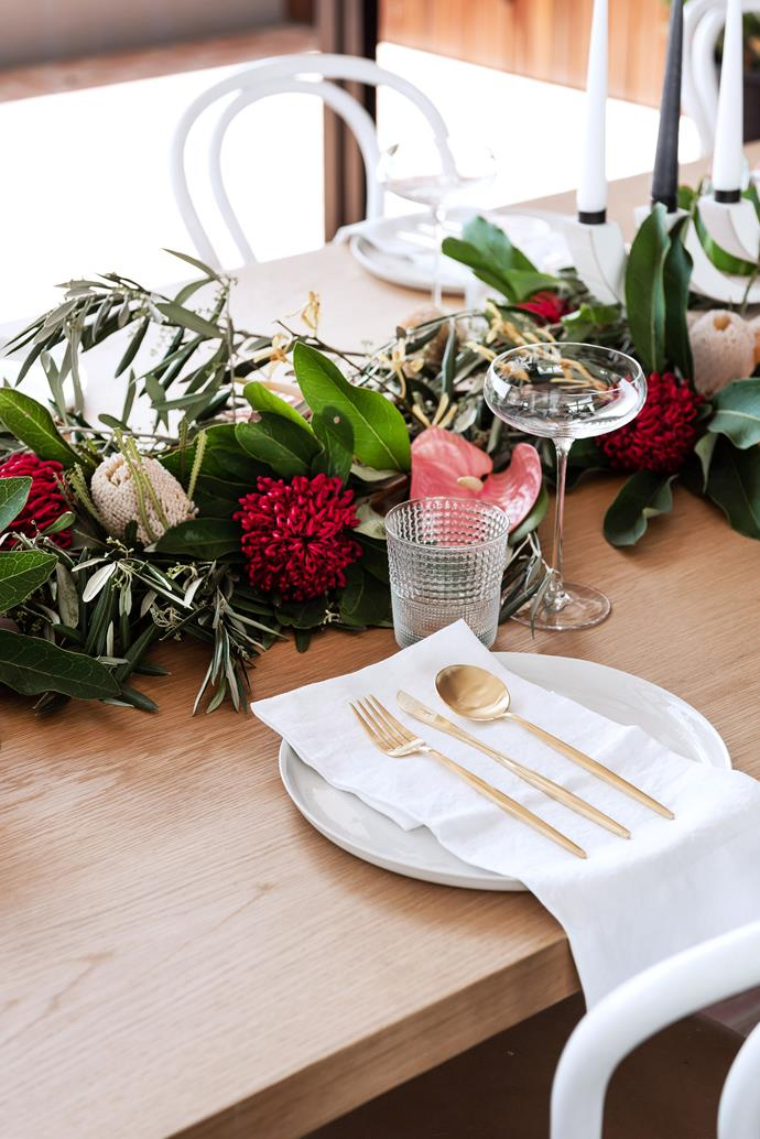 A table runner made from green foliage, dotted with rich red flowers, makes for an elegant Christmas table centrepiece.
