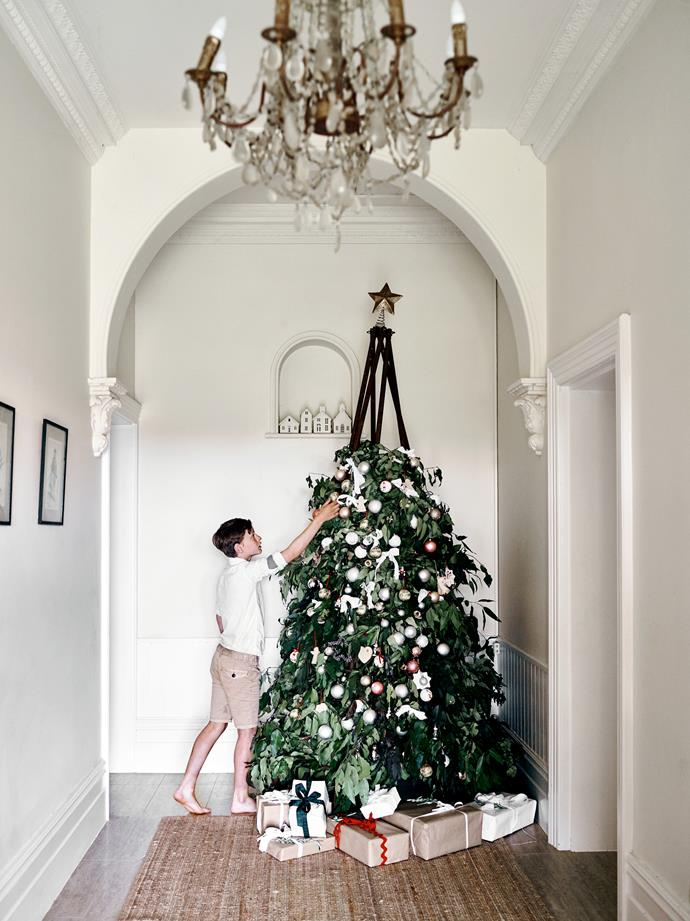 """Gus helps decorate the tree. """"It's inspired by my love of rust, natural woven fibres, flowers and foliage,"""" says his mother Kate. The tree frame was created by Random Recycled."""