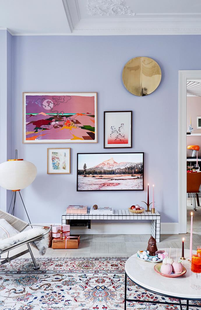 The soft purple walls of this home are the perfect background for a bold gallery wall of art. Pieces from Eske Kath (left), Cathrine Raben Davidsen (right) and Jakob Steen (below left) are joined by the Imago brass mirror object. The clever Samsung 'The Frame' TV (below right) also displays works of art when not in use.
