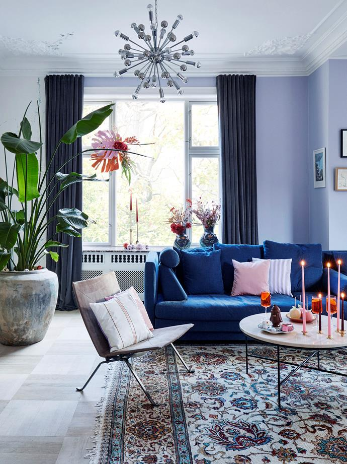 The sofa from Eilersen, together with the rich velvet curtains, creates a cosy and inviting vibe, while the mid-century modern Sputnik chandelier by Paul de Haan for Jolina draws the eye upwards and centres the room.