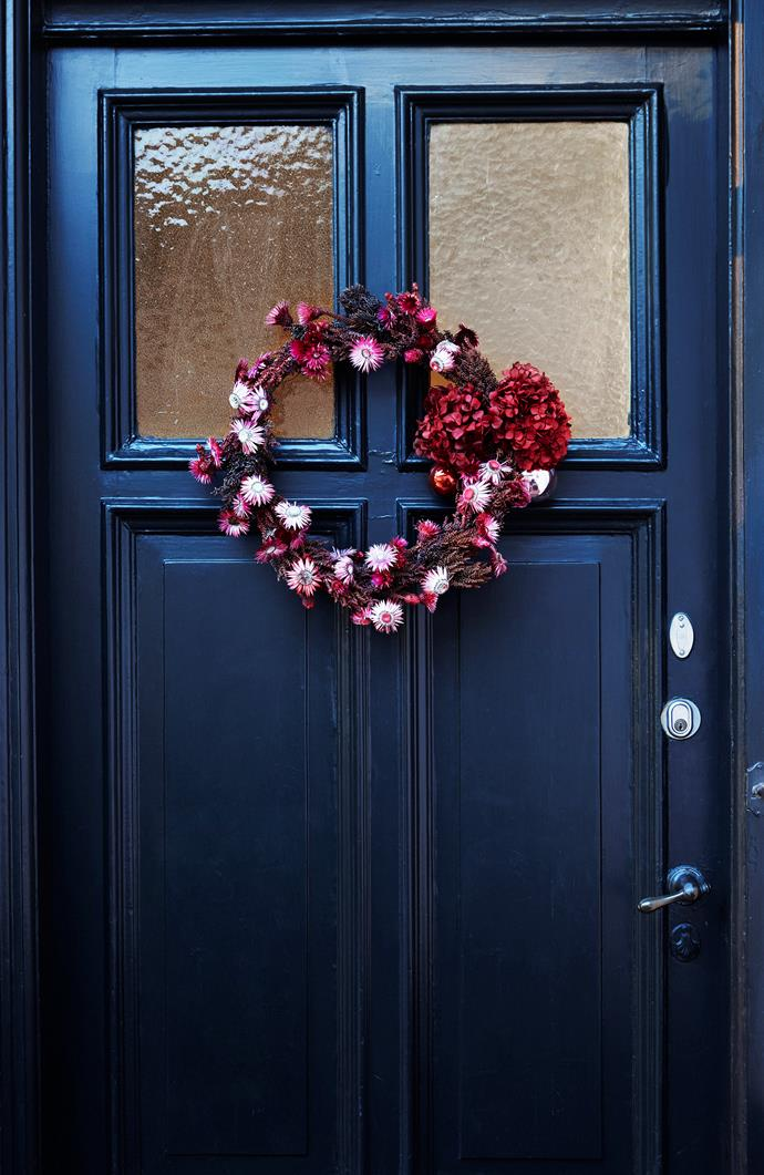 "A Bike & Bloom [fresh flower wreath](https://www.homestolove.com.au/how-to-make-a-fresh-flower-wreath-4448|target=""_blank"") contrasts against the navy front door and is decorated with spray-painted helichrysum and hydrangeas."