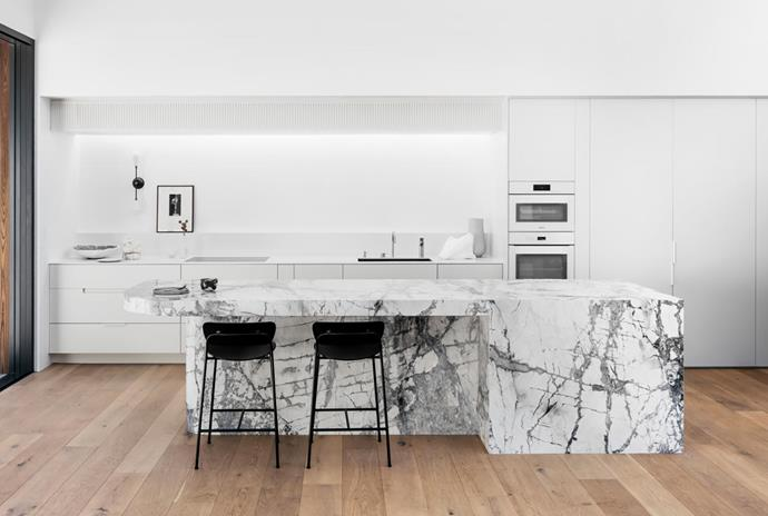 The kitchen island bench is clad in Cote d'Azur marble from CDK Stone with &Tradition 'Pavilion' stools from Cult. Fisher & Paykel integrated fridge and freezer in custom ribbed joinery. Apparatus 'Dyad' wall sconce from Criteria. Artwork by Laura Ellenberger from .M Contemporary.