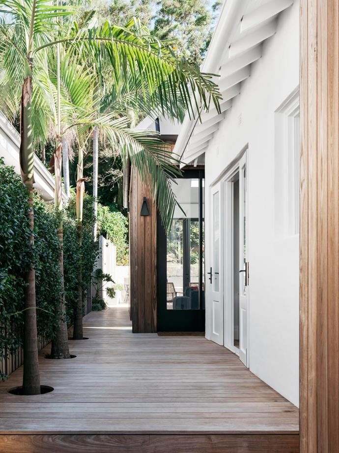 The new entrance is along the side of the house on a decked path planted with palm trees and star jasmine. Rakumba 'Standley' wall light from Design Nation. Exterior is clad in SculptForm Burnt Ash in Sorrento Wide.