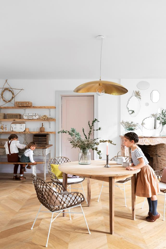 In the family's playroom, the children gather to draw and practise the piano and harp. A second-hand table with woven rattan armchairs from Maisons Du Monde and cushions from Inspirations by la Girafe take centrestage under the matte-brass pendant light from Gervason