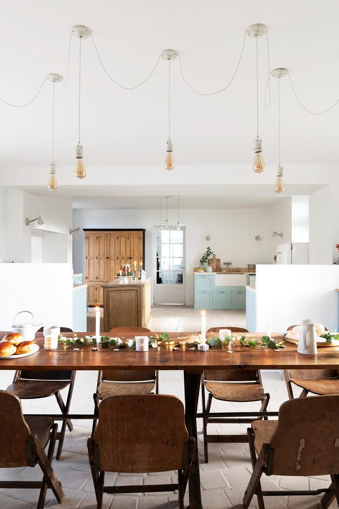 The vast kitchen and dining room is decorated with a mix of second-hand workshop cabinets and homemade furniture, which blend seamlessly with the kitchen's soft turquoise cabinetry and rustic stone tiles. The dining table and chairs – both second-hand market finds – sit under custom pendant lights from Flabala Luminaires.