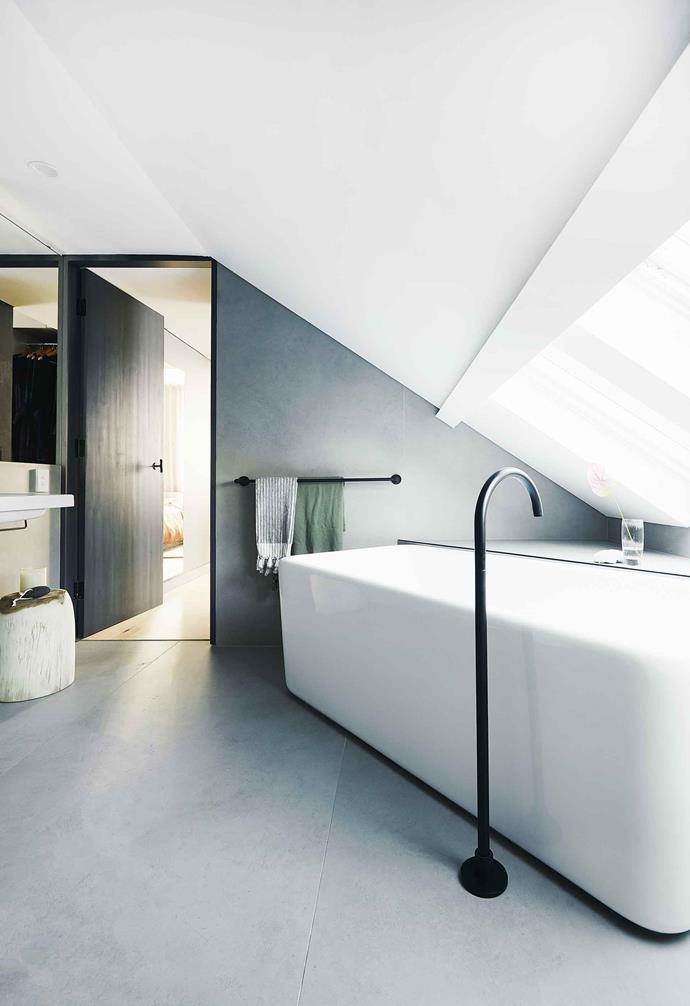 "Placed directly under the roof, the ensuite in this incredible [Scandi-noir style house](https://www.homestolove.com.au/scandi-noir-house-20344|target=""_blank"") makes the most of its prime location with strategically placed skylights that flood the bathroom in light. The stark white of the ceiling creates a dynamic contrast with the light grey walls and floor tiles, as well as the black accents in the space."