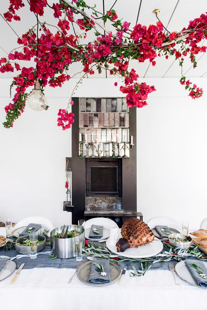 If you're dining formally outside, consider what natural features you can use to add a festive touch. Trees make the perfect place to hang Christmas baubles and you can use wreaths or festive foliage like this bougainvillea canopy to dress up your home exterior.