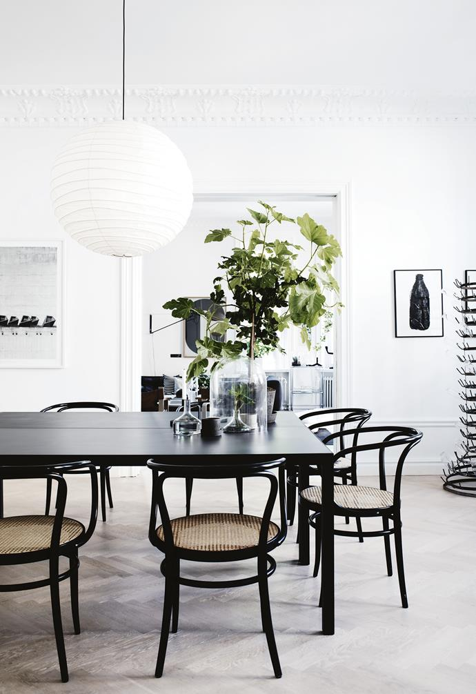 "Throughout the elegant home, the walls are white and the scheme [monochromatic](https://www.homestolove.com.au/monochrome-interiors-trending-on-pinterest-6871|target=""_blank""), with a charcoal rug and low-slung B&B Italia sofa in the living space teamed with two vintage Børge Mogensen 'Spanish' chairs in leather.<br><br>**Dining room** Classic Le Corbusier Thonet chairs form a link between the contemporary MDF Italia dining table and the traditional timber herringbone parquetry floor."